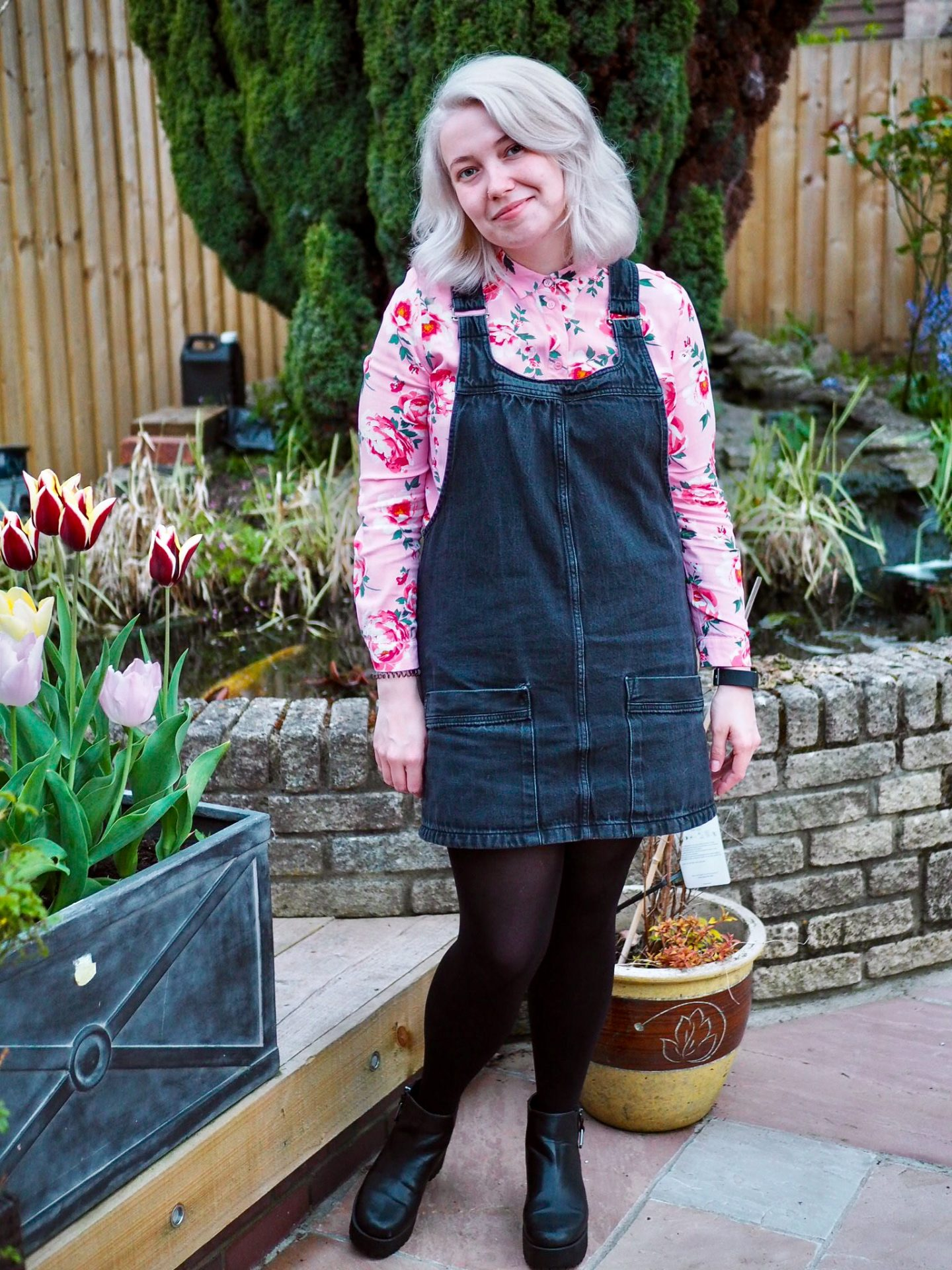Blonde girl in garden in second hand shirt and pinafore