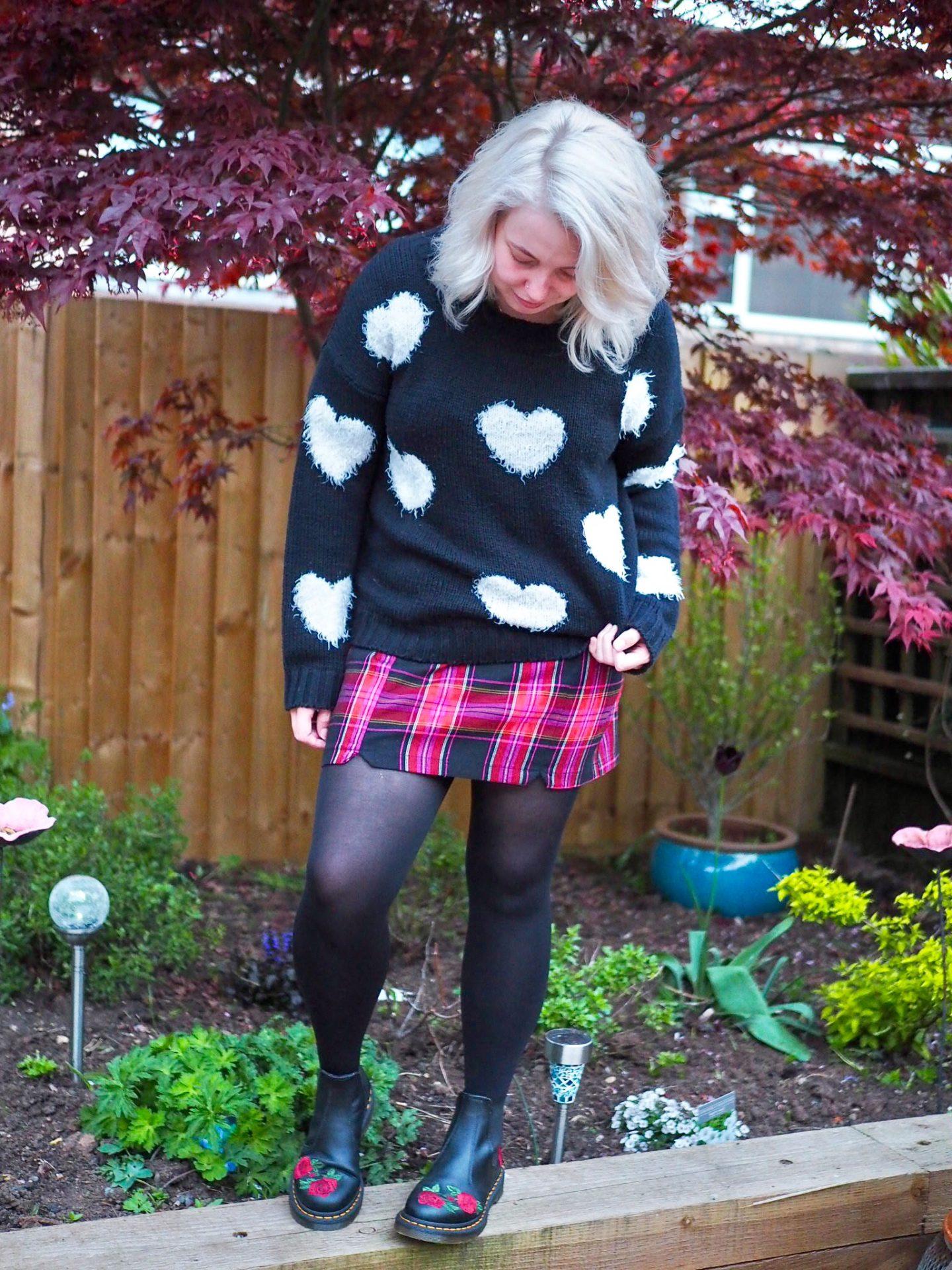 Blonde standing girl in second hand heart jumper and tartan skirt